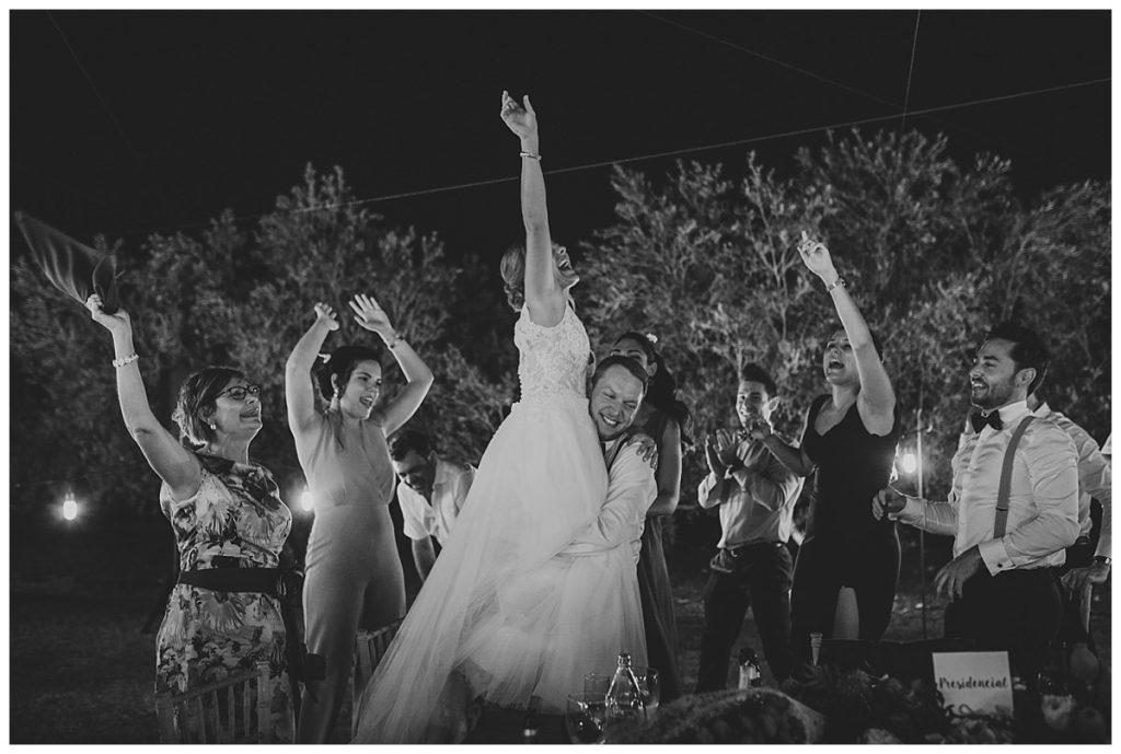 Fotografía de boda pareja con amigos levantando las manos celebrando en la cena