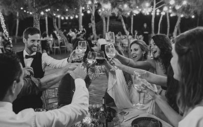 Fotografía de boda pareja brindando en la cena con sus amigos